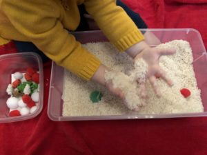 toddler hands close up in rice sensory bin