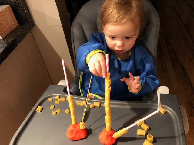 toddler threading pasta for fine motor and language development
