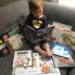 Toddler surrounded by free books from literacy program