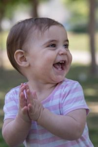 Baby clapping imitation for early language development