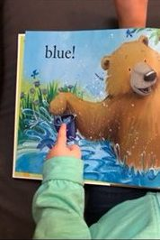 early literacy and language development toddler pointing at book