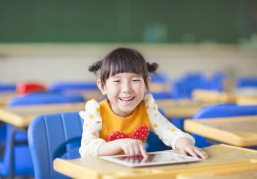 smiling kid using videos for speech therapy